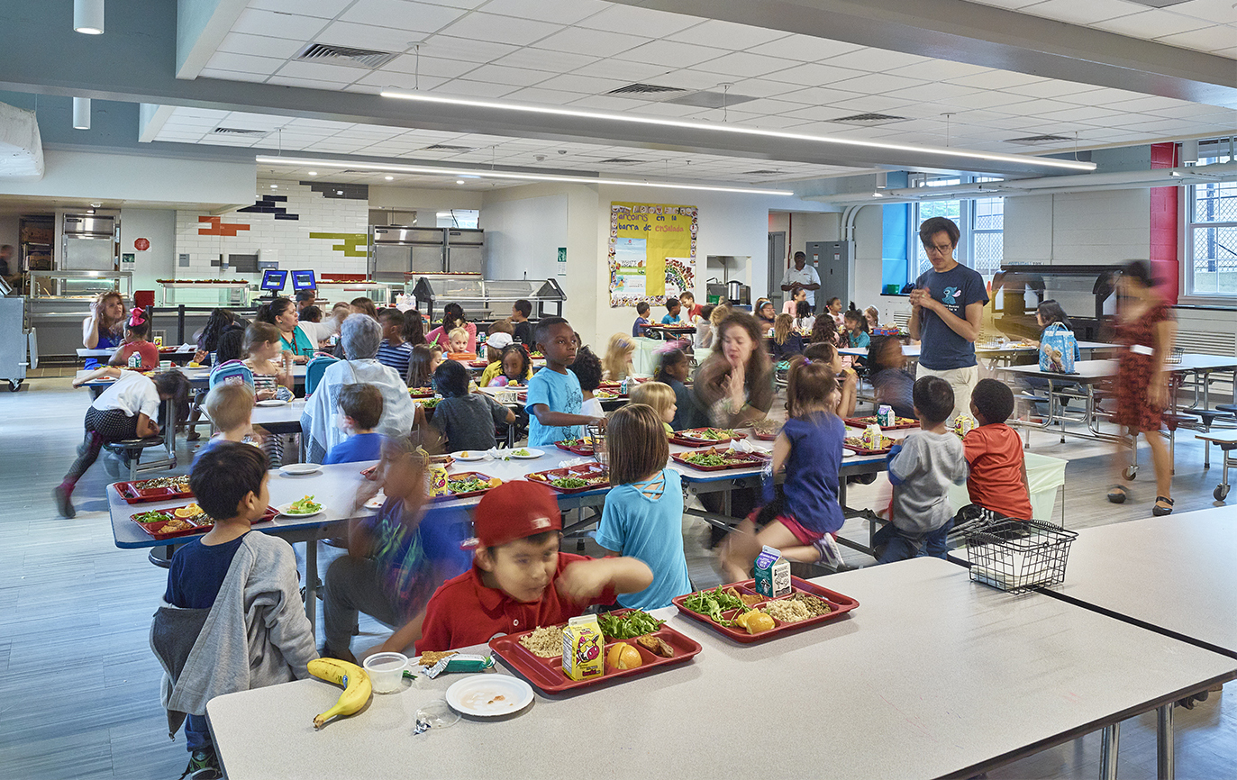 A large group of elementary school kids eats in a cafeteria
