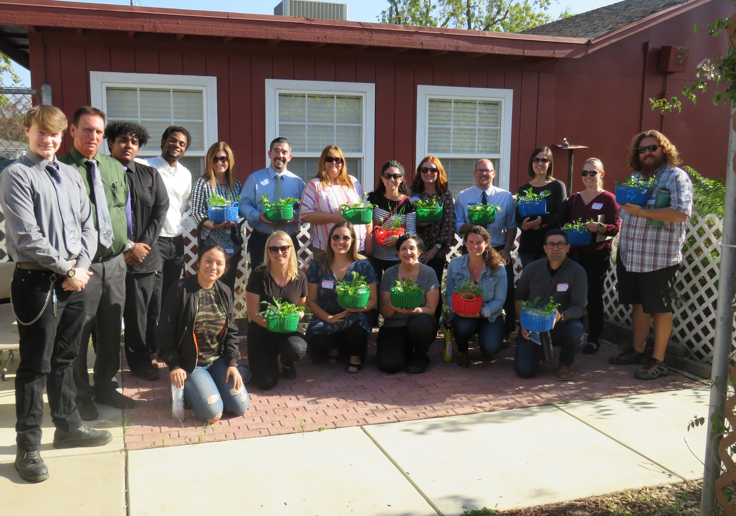 Teachers and students pose outdoors, holding plants