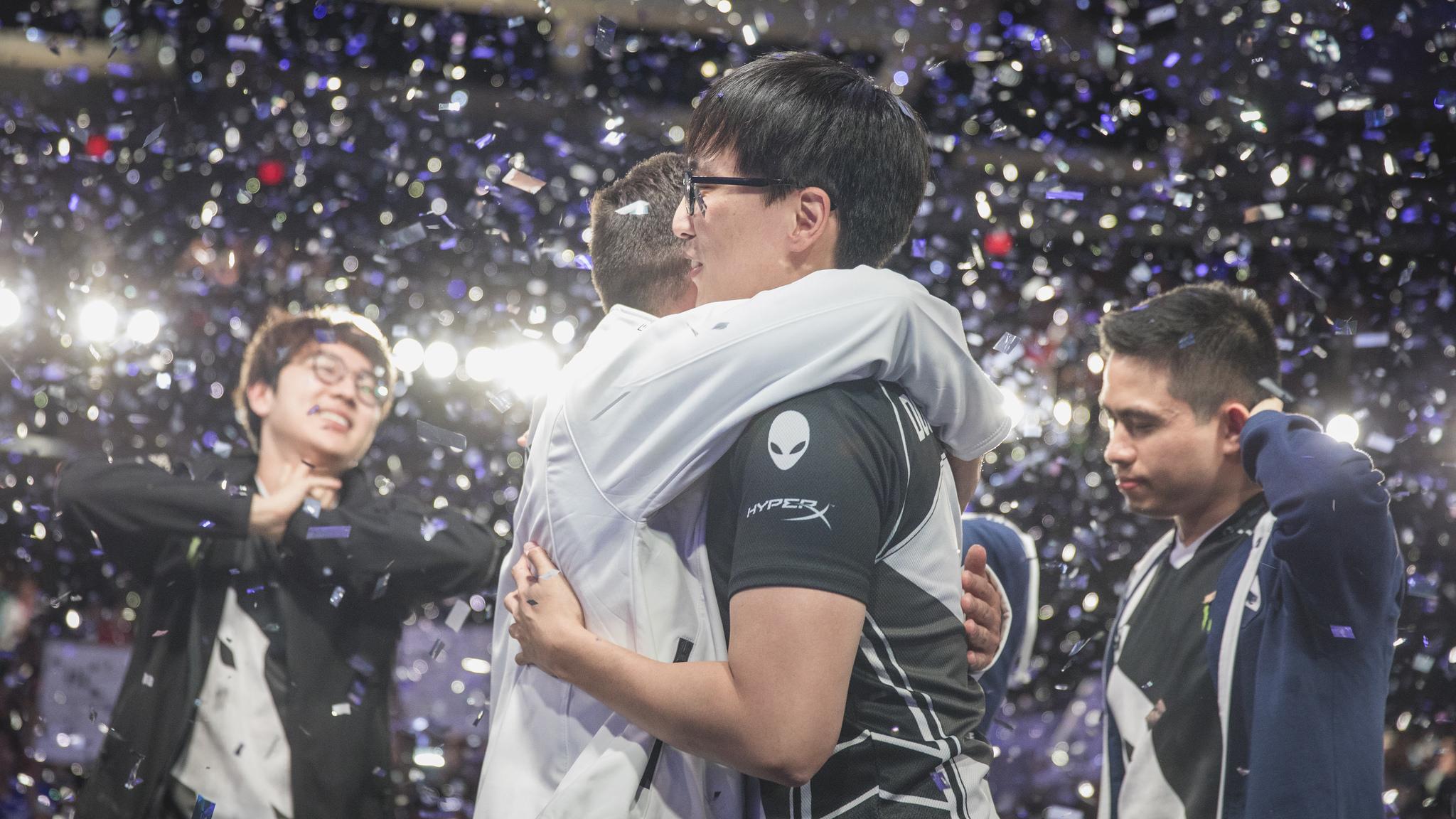 College boys hugging after winning esports championship as confetti falls.