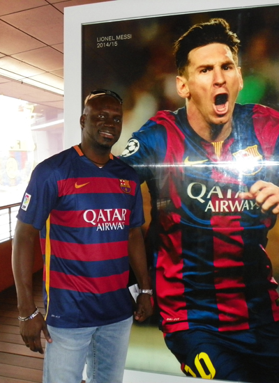 [Dane poses with a picture of Lionel Messi at FC Barcelona's Stadium