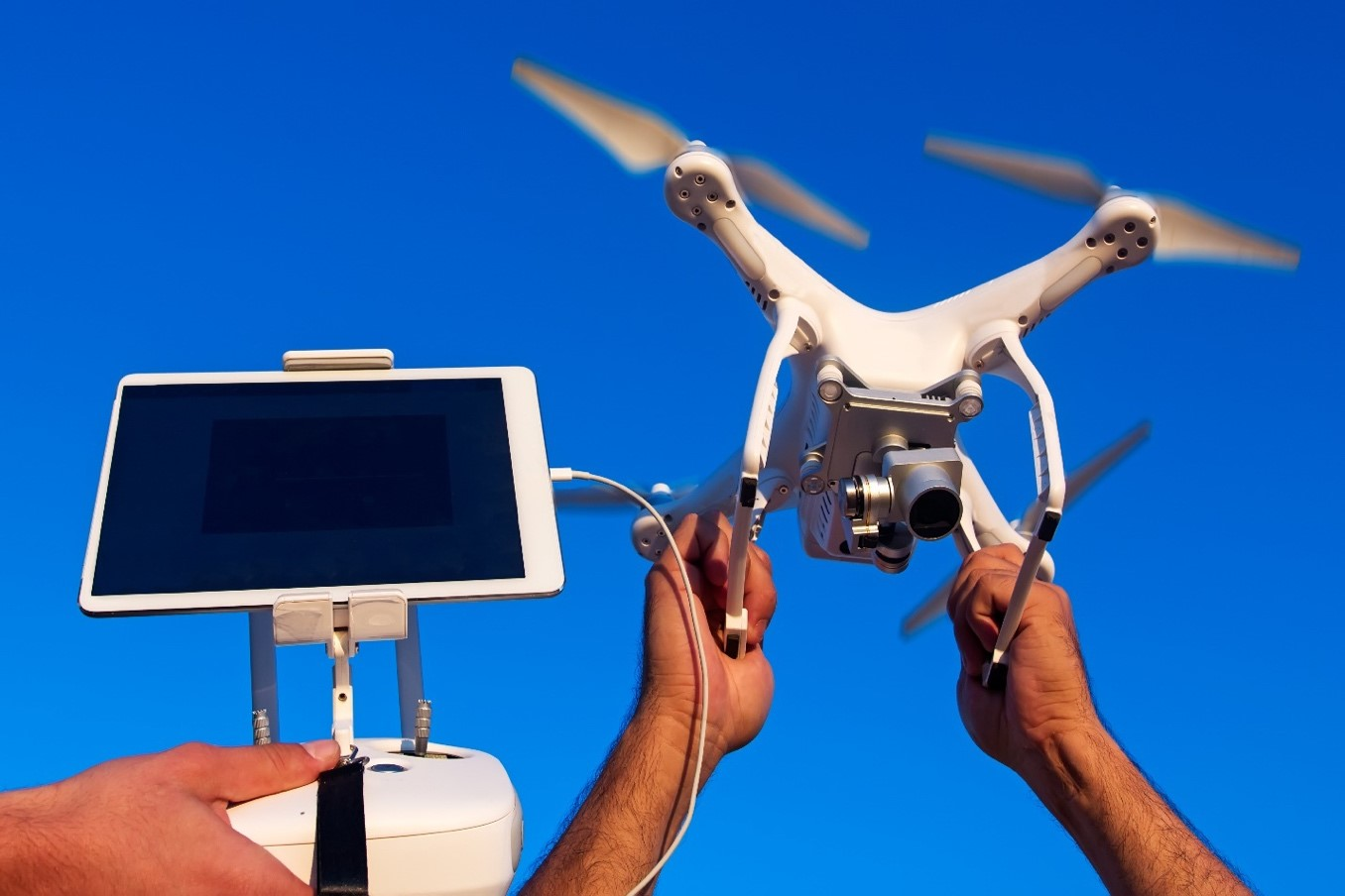 Drone powered by tablet taking off from hands