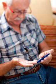 A senior man tests his blood sugar levels