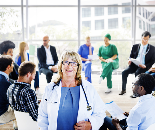 Female doctor standing in front of a support group. Image: awpixel.com/Shutterstock.com.